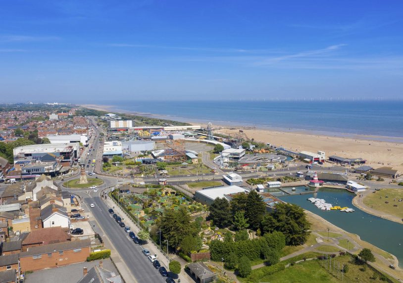 Aerial photo of the town centre of Skegness showing the pier on the sandy beach near fairground rides in the East Lindsey district of Lincolnshire, England on a beautiful sunny summers day.