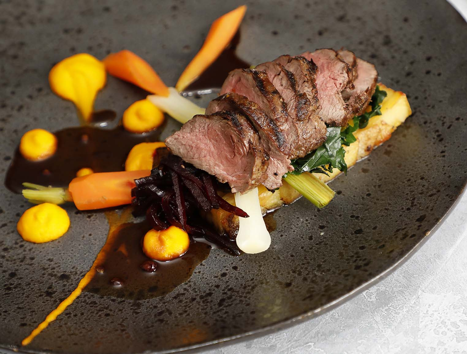Venison steak with curly kale, sweet pickled beetroot, carrot purée and juniper jus.