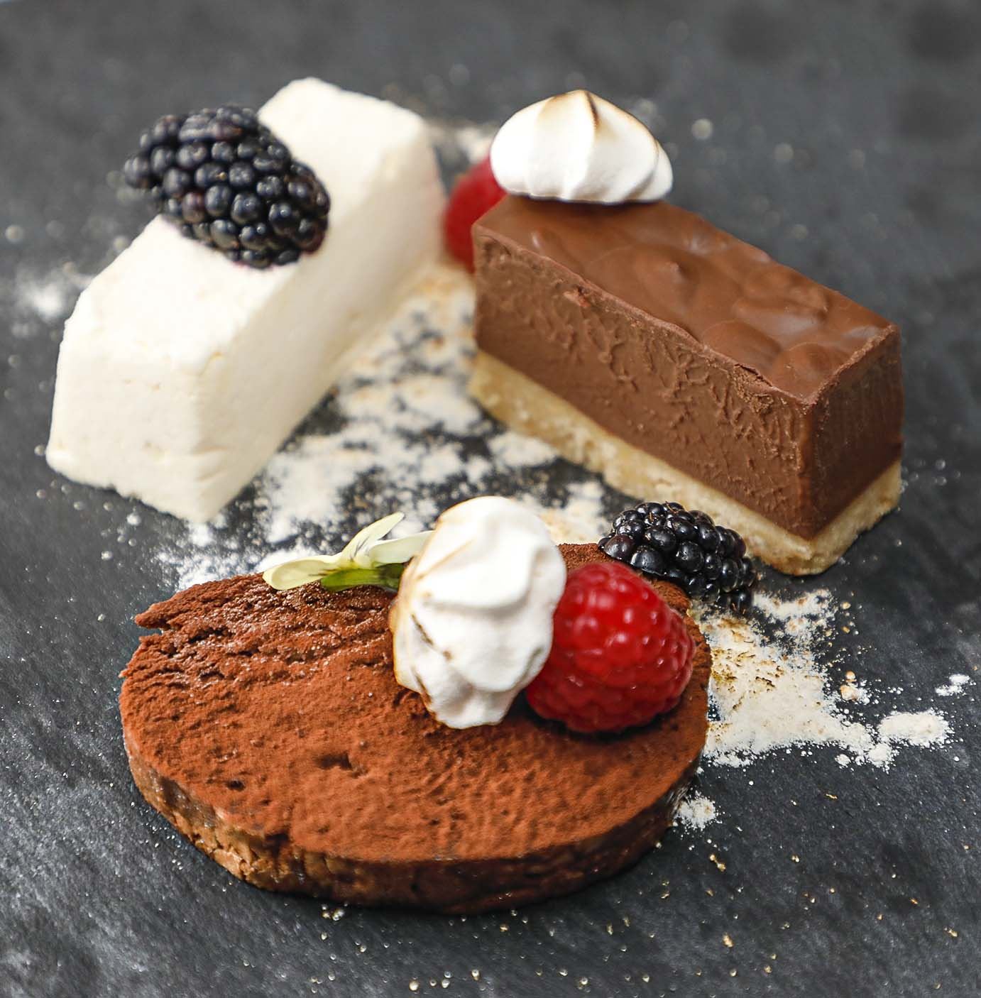 Trio of chocolate, comprising chocolate delice, white and vanilla chocolate parfait, chocolate roulade.
